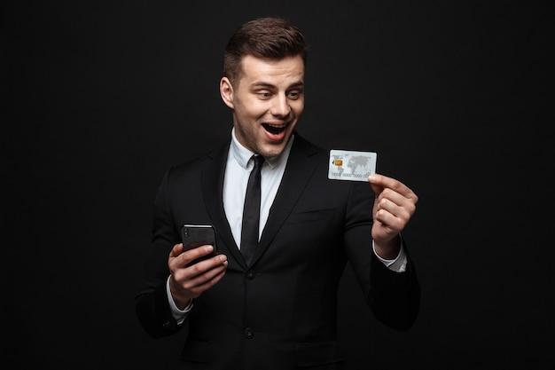自信を持って魅力的なビジネスマンが黒い壁の上に孤立して立っているスーツを着て、携帯電話を使用して、プラスチックのクレジットカードを示しています