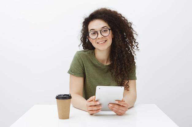 Уверенная в себе привлекательная кудрявая брюнетка в модных очках сидит за столом, пьет чай или кофе и держит цифровой планшет