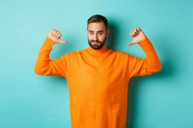 Confident attractive guy pointing at himself, show-off or brag, standing
