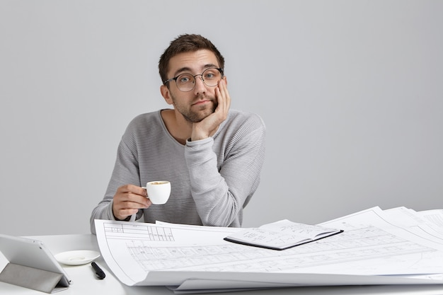 Fiducioso uomo attraente, tiene la tazza di cappuccino, si siede al tavolo circondato da schemi e schizzi