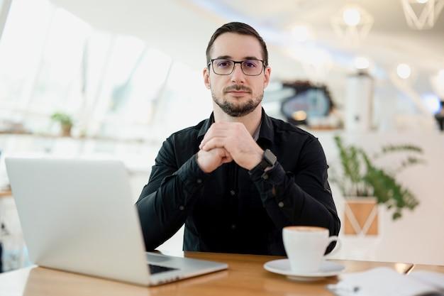 カメラを見て自信を持って魅力的な男。現代のラップトップと木製のテーブルの上のカプチーノのカップ。背景の明るいスマートコーヒーショップのインテリア。喫茶店で働くフリーランサーの男。