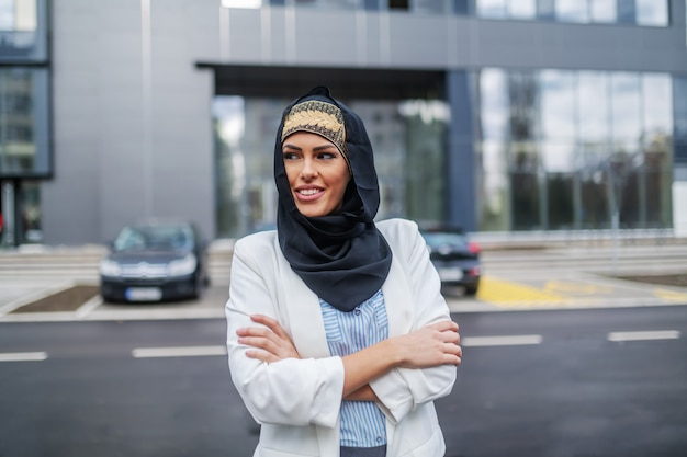 Уверенно привлекательный стильный мусульманский бизнесвумен, стоящий перед корпоративным зданием со сложенными руками и глядя в сторону.