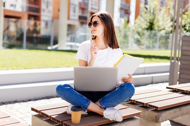 Confident attractive woman sitting on bench in park and messaging in social media while writing in notebook during coffee break