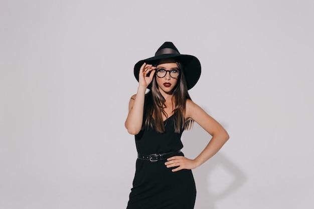Fiduciosa donna attraente con lunghi capelli castani che indossa cappello e occhiali con rossetto di vino
