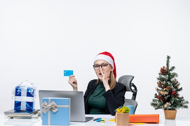 Уверенная в себе привлекательная женщина в шляпе санта-клауса и в очках сидит за столом и держит банковскую карту и сплетничает в офисе