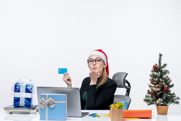 Confident attractive woman with santa claus hat and wearing eyeglasses sitting at a table and holding bank card and sending kiss in the office