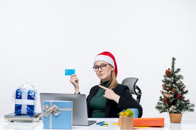 Confident attractive woman with santa claus hat and wearing eyeglasses sitting at a table and pointing bank card in the office