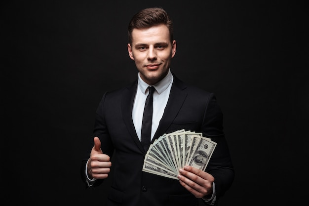Confident attractive young businessman wearing suit standing isolated over black wall, showing money banknotes, thumbs up