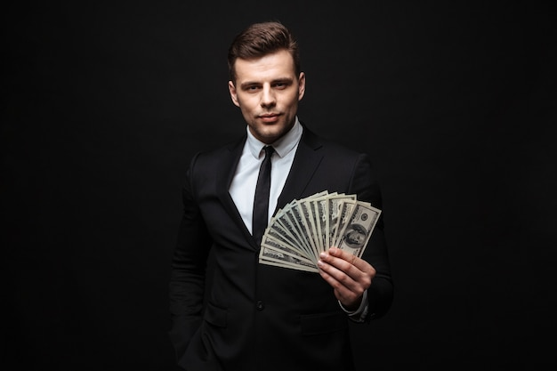 Confident attractive young businessman wearing suit standing isolated over black wall, showing money banknotes
