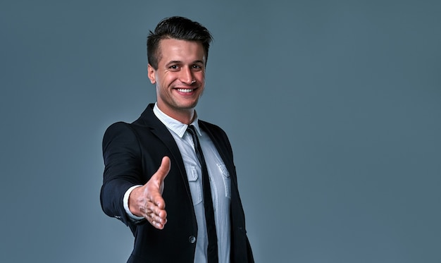 Confident attractive young businessman wearing suit standing isolated over gray background, holding outstretched hand for greeting.