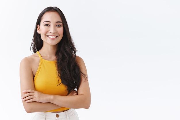黄色のトップで自信を持って、魅力的な若い発信アジアの女性、クロスハンドの胸のようにフレンドリーで幸せな笑顔、白い背景の上にポーズをとって自信を持って、生意気なポーズ、決意の表情