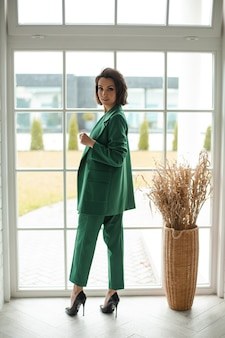 Confident attractive young woman standing in the room in costume and high heeled shoes and turning back. style and fashion concept