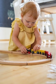 Confident baby girl in dress playing wooden train railways maria montessori ecological materials