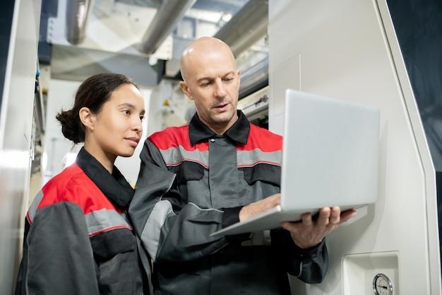 젊은 여성 부하에게 새로운 자료를 발표하는 동안 노트북을 들고 작업복을 입은 자신감 있는 대머리 성숙한 감독
