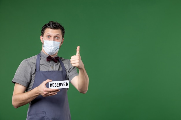 Confident banquet server in uniform with medical mask and showing reserved icon making ok gesture on green background