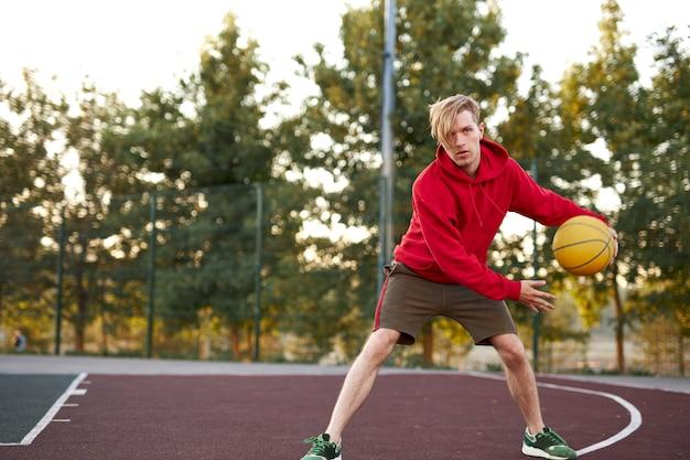自信を持ってバスケットボールのゲーマーが屋外で遊ぶ