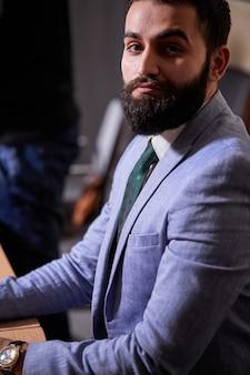 自信を持ってひげを生やしたブルネットの幹部が真剣に見て、ビジネスの人々の概念を見てカメラにポーズ