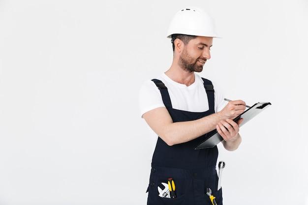 Уверенный бородатый мужчина-строитель в комбинезоне и каске стоит изолированно над белой стеной и делает заметки в блокноте