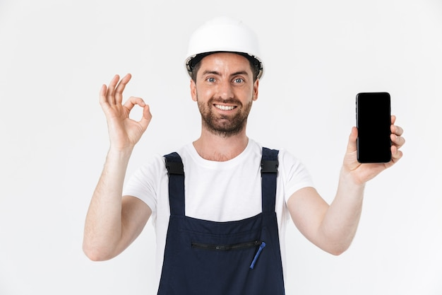 Уверенный бородатый мужчина-строитель в комбинезоне и каске, стоящий изолированно над белой стеной, показывая хороший жест и пустой экран мобильного телефона