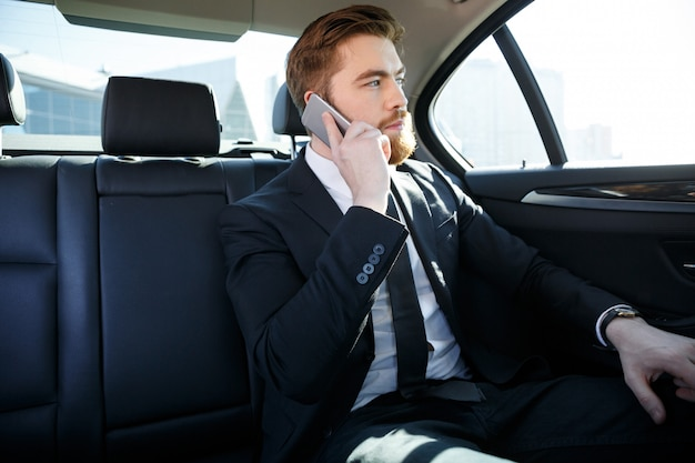 Уверенный бородатый бизнесмен разговаривает по мобильному телефону