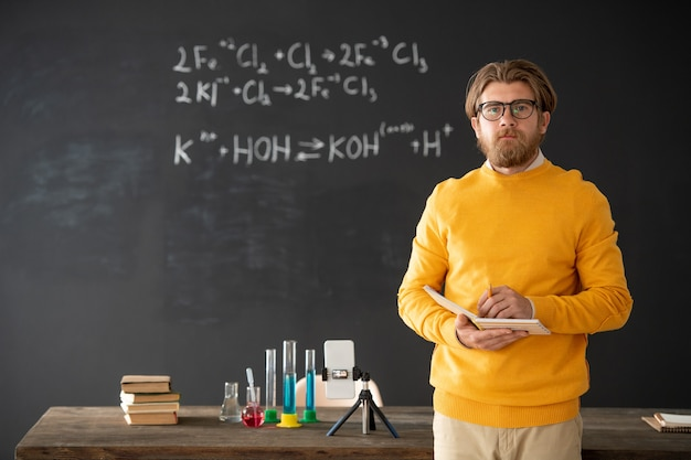 펼친 책이 칠판에 테이블에 앉아 온라인 학생들을위한 강의를 준비하는 자신감 수염 화학 교사