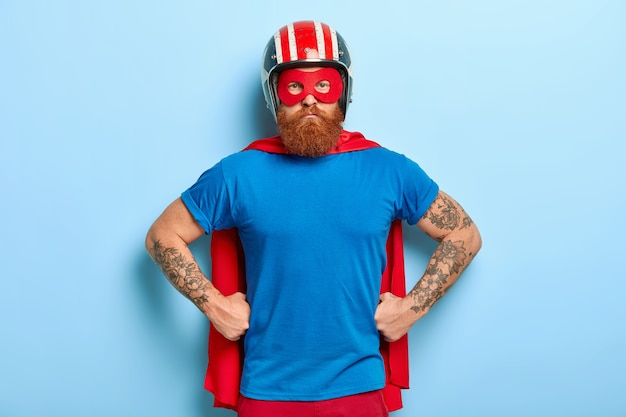 Confident bearded guy keeps hands on waist, ready for defense, look with strong powerful look directly at camera, wears helmet