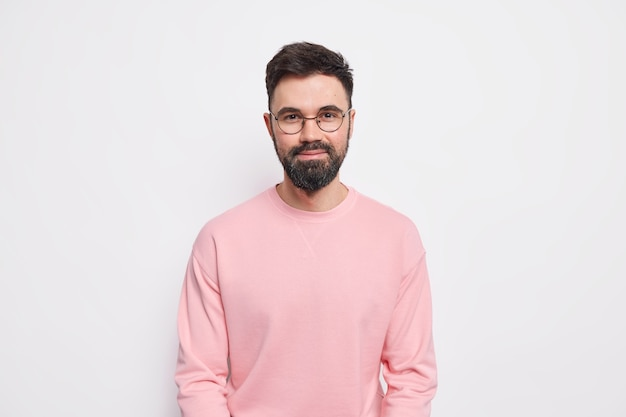 Confident bearded macho man looks pleased, has friendly kind grin on face wears round spectacles pink jumper