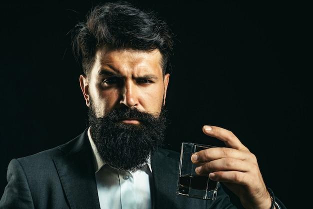 Уверенный бородатый мужчина в черном костюме с бокалом алкоголя