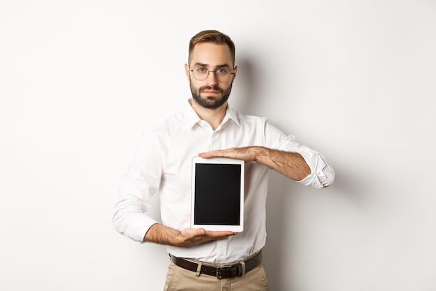 Уверенно бородатый мужчина показывает экран цифрового планшета, демонстрирует приложение, стоя