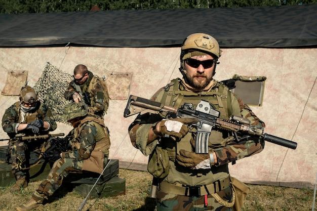 위장 복장과 헬멧을 쓰고 소총을 들고 거리를 바라보는 자신감 있는 수염 난 군인
