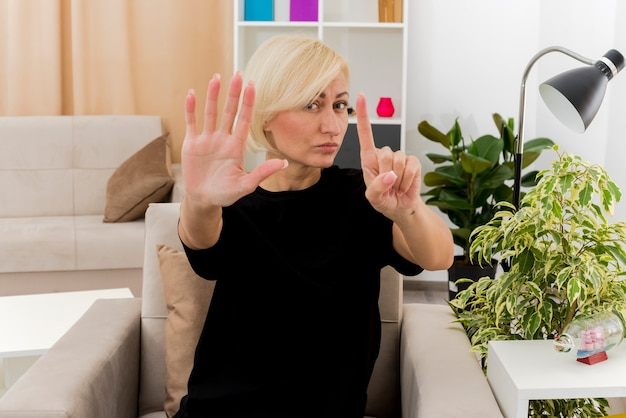 Fiduciosa bella bionda donna russa si siede sulla poltrona gesticolando sei con le dita