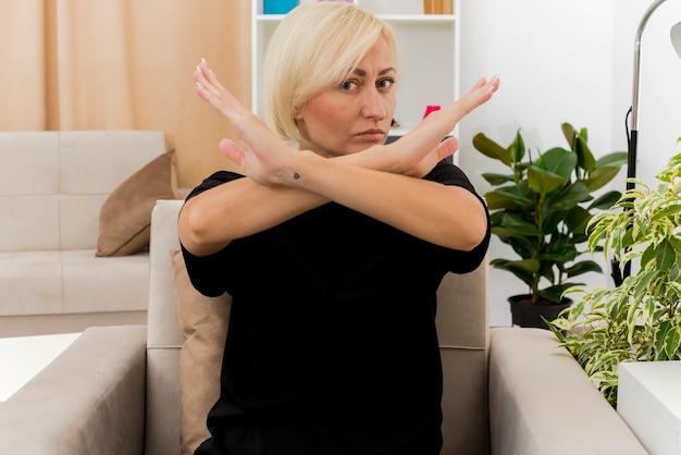 自信を持って美しい金髪のロシアの女性は、兆候を身振りで示す腕を組んで肘掛け椅子に座っています