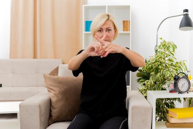 自信を持って美しい金髪のロシアの女性は、兆候を身振りで示す指を交差させる肘掛け椅子に座っています