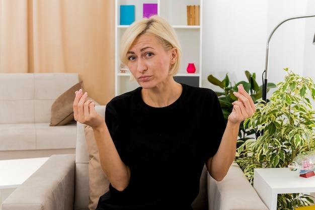 自信を持って美しい金髪のロシアの女性が両手でお金の手振りを身振りで示す肘掛け椅子に座っています。