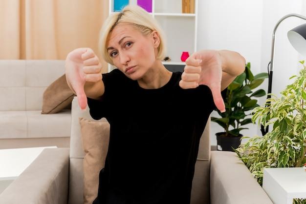 Уверенная красивая русская блондинка сидит на кресле большими пальцами вниз и смотрит двумя руками