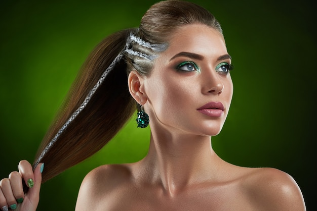 シルバー色と緑の光沢のある化粧ポーズの要素を持つスタイリッシュな散髪と自信を持って美しいブルネットの少女。大きな丸いイヤリングがよそ見、髪を手に持った女性。美しさ。