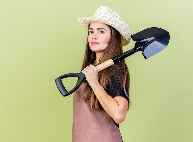 オリーブグリーンの背景で隔離の肩にスペードを置くガーデニング帽子を身に着けている制服を着た自信を持って美しい庭師の女の子