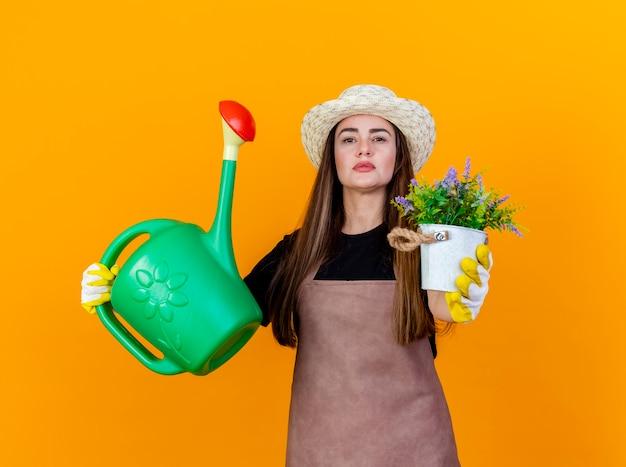 オレンジ色の背景に分離されたカメラで水まき缶を上げ、flwerpotで花を差し出す手袋と制服と園芸帽子を身に着けている自信を持って美しい庭師の女の子