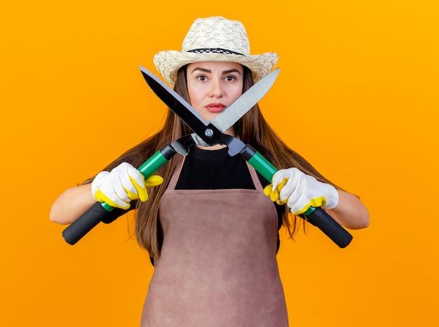 Fiduciosa bella ragazza giardiniere che indossa uniforme e cappello da giardinaggio con i guanti che tengono i clippers isolati su priorità bassa arancione