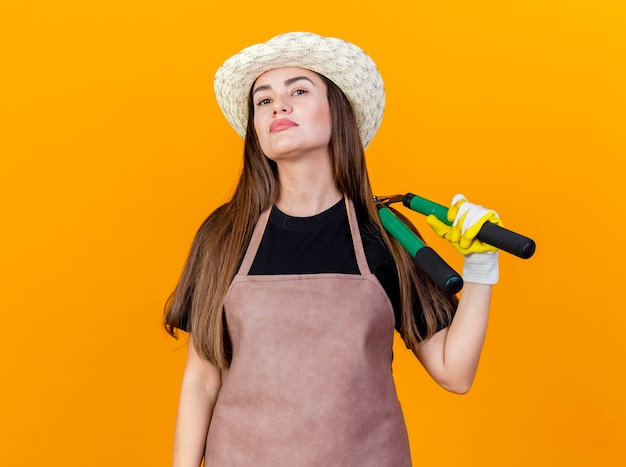 Fiduciosa bella ragazza giardiniere che indossa uniforme e cappello da giardinaggio con guanti che tengono i clippers sulla spalla isolati su sfondo arancione
