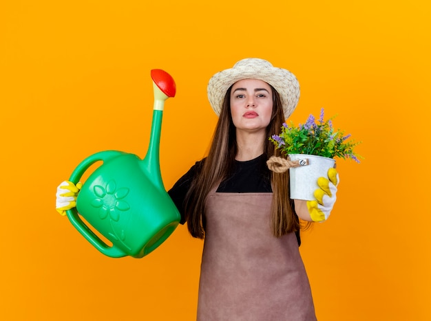 Confident beautiful gardener girl wearing uniform and gardening hat with gloves raising watering can and holding out flower in flwerpot at camera isolated on orange background