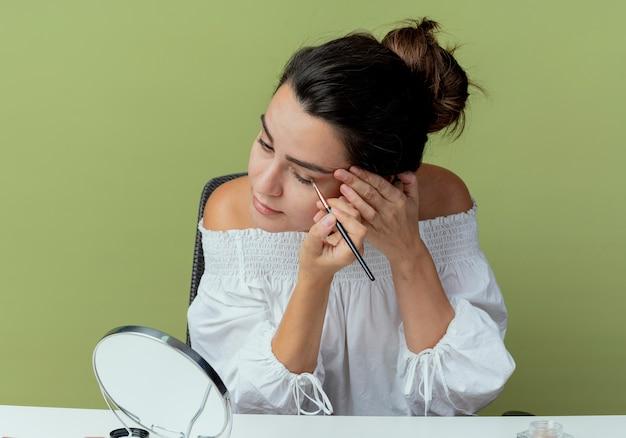 Fiduciosa bella ragazza si siede a tavola con strumenti di trucco guardando allo specchio applicando ombretto con pennello trucco isolato sulla parete verde