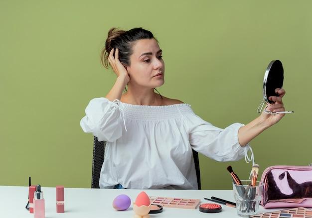 Fiduciosa bella ragazza si siede al tavolo con strumenti di trucco mette la mano sulla testa tiene e guarda allo specchio isolato sulla parete verde