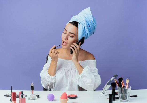 Уверенная в себе красивая девушка, завернутая в полотенце для волос, сидит за столом с инструментами для макияжа, держа и применяя блеск для губ, разговаривает по телефону, изолированному на фиолетовой стене