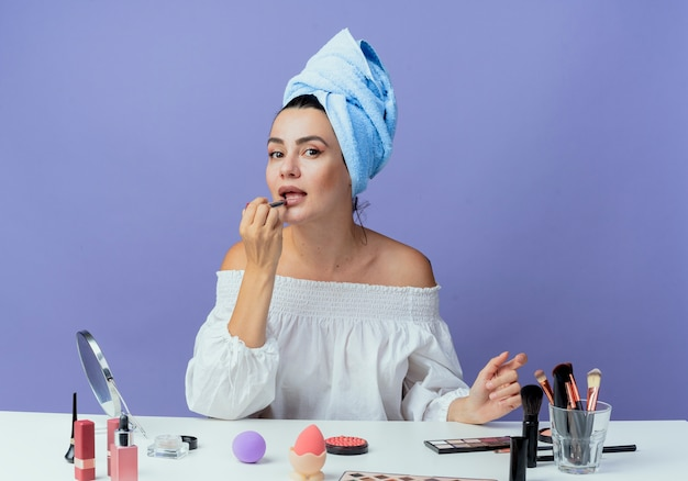 Confident beautiful girl wrapped hair towel sits at table with makeup tools holding and applying lipstick looking isolated on purple wall