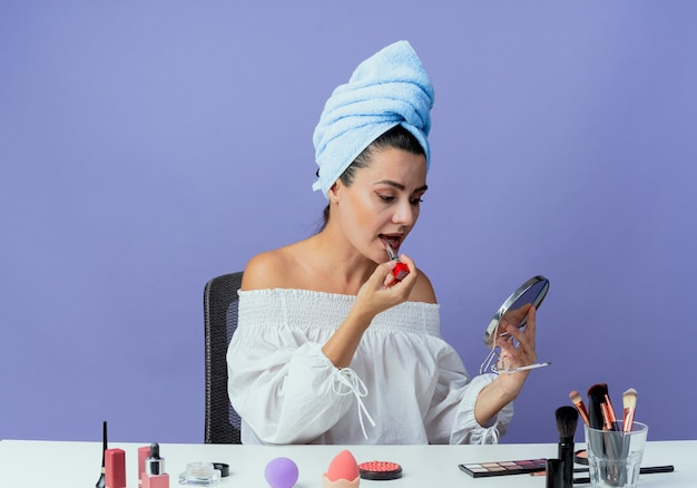 Confident beautiful girl wrapped hair towel sits at table with makeup tools holding and applying lipstick looking at mirror isolated on purple wall