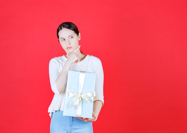 ギフト用の箱を持って考える自信のある美しい女性
