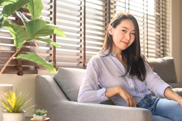 ソファに座っている自信を持って美しい笑顔のアジアの女性