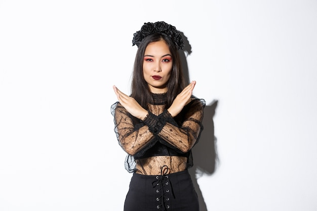 Fiduciosa bella donna in abito gotico nero che mostra il gesto trasversale, disapprovare e fermare qualcosa di brutto, in disaccordo con qualcuno su halloween, in piedi su sfondo bianco.