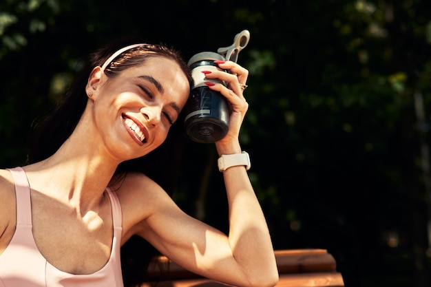 Confident, beautiful woman resting after workout outdoor and drinks water from a bottle, leads a healthy lifestyle